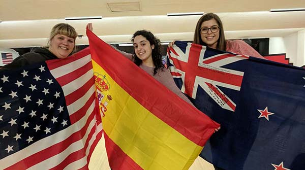 Host Mom and Two Exchange Students Holding Country Flags