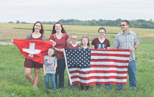 Family with exchange student holding American and Swiss Flags in a field