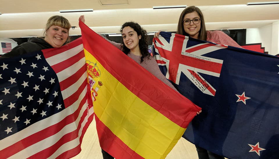 Local Coordinator with two exchange students holding flags
